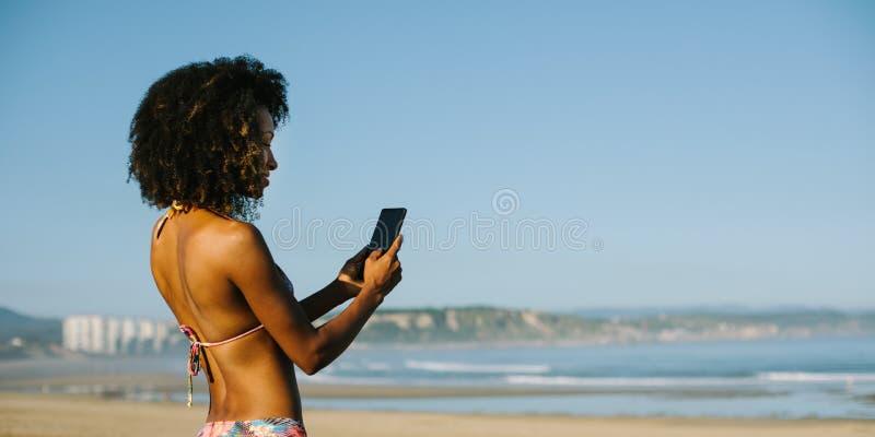 De jonge vrouw die van het afrohaar smartphone gebruiken bij het strand stock foto's