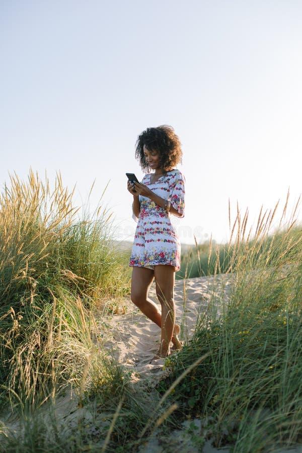 De jonge vrouw die van het afrohaar smartphone gebruiken bij het strand stock foto
