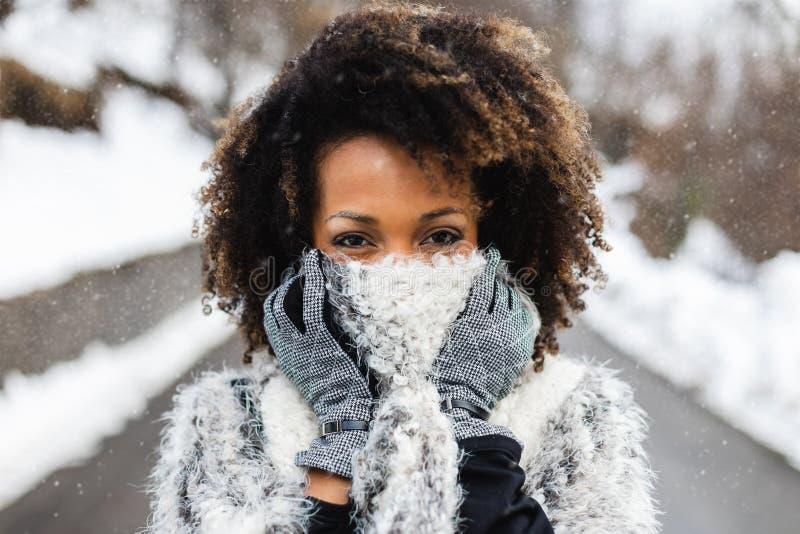 De jonge vrouw die van het Afrohaar wolsjaal dragen onder de sneeuw in de winter royalty-vrije stock afbeelding