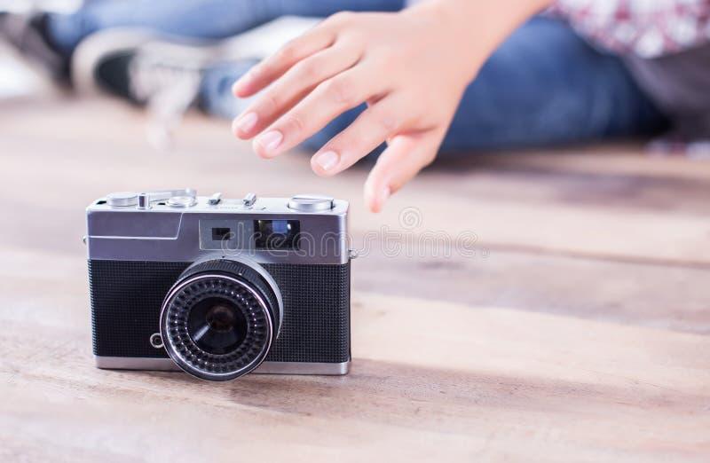 De jonge vrouw die van de hipsterfotograaf foto nemen en bekijkt camerazitting op houten vloer stock fotografie