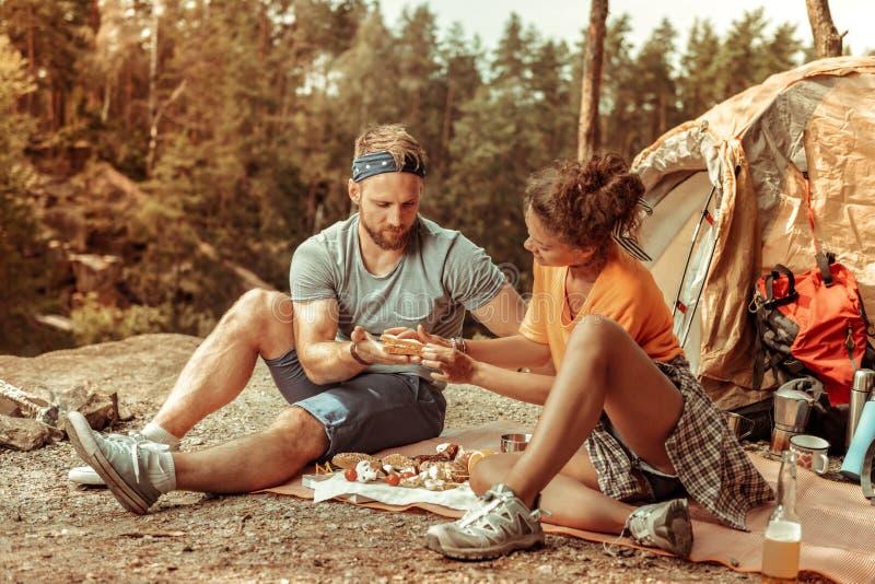 De jonge vrouw die van Nice een sandwich voor haar vriend doen stock afbeeldingen