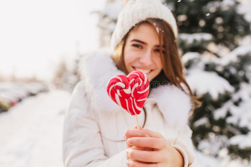De jonge vrouw die van de portretwinter roze hart houden lollypop, koelend op straathoogtepunt met sneeuw in zonnige ochtend wit stock foto