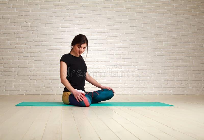 De jonge vrouw die yogaoefeningen doen die in lotusbloem zitten stelt stock fotografie