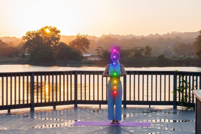 De jonge vrouw doet yoga op de zonsopgang stock afbeeldingen