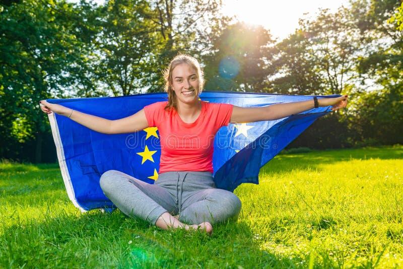 De jonge vrouw draagt erachter een Europese vlag en glimlacht stock foto