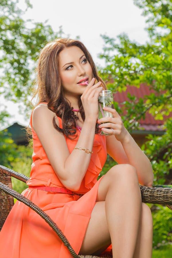De jonge vrouw drinkt cocktail stock foto