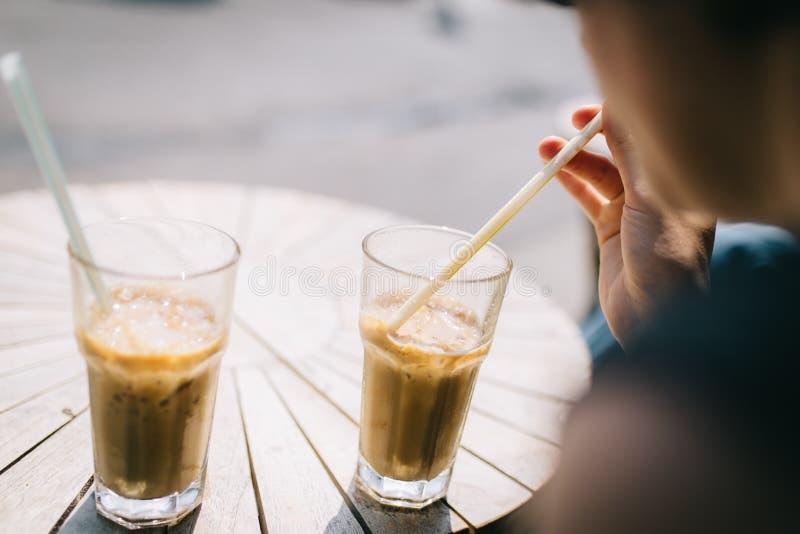 De jonge vrouw drinkt een zoete bevroren koffie stock foto's