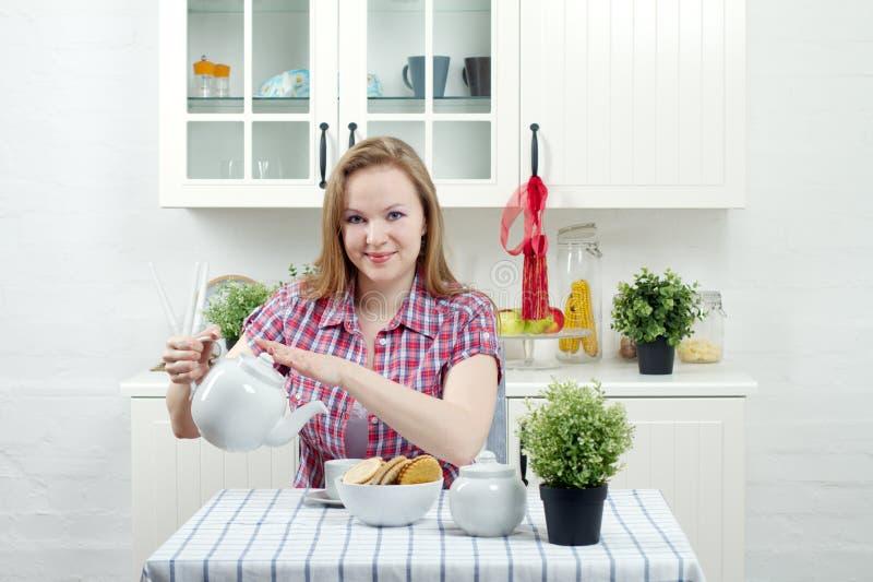 De jonge vrouw drinkt thee stock foto