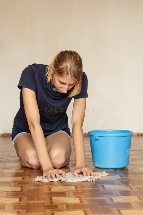 De jonge vrouw dweilt de vloer stock foto's