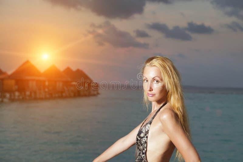 De jonge vrouw in een badpak bij zonsondergang op achtergrond van het overzees en de silhouetten van huizen over water royalty-vrije stock afbeelding