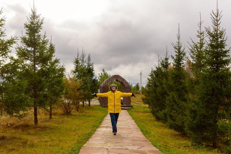 De jonge vrouw in een gele regenjas die langs de weg in het Park in bewolkt weer met van hem lopen dient de regen in verheugt zic stock foto's