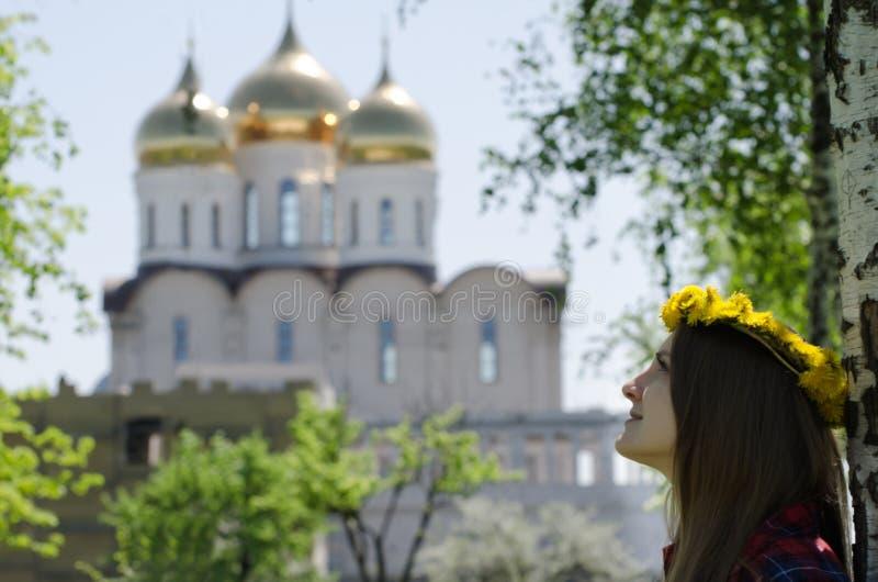 De jonge vrouw in een kroon van paardebloemen bekijkt een orthodoxe tempel, de lente stock fotografie