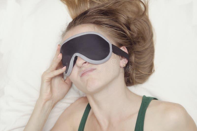 De jonge vrouw in een masker voor slaap wil niet ontwaken stock afbeelding