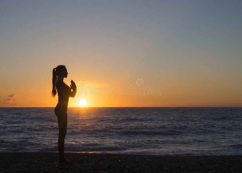 De jonge vrouw in een mediterende yoga stelt het overzien van de mooie zonsondergang De geestconcept van het meningslichaam royalty-vrije stock afbeelding
