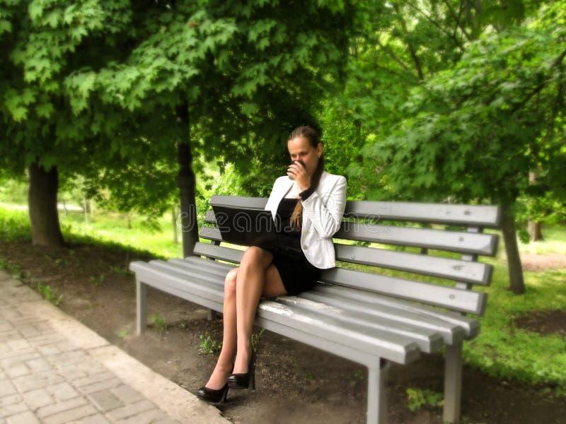 De jonge vrouw in een pak drinkt koffie en de werken aangaande laptop terwijl het zitten op een bank in het park, zijaanzicht Een stock foto