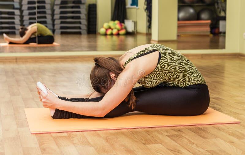 De jonge vrouw in een yoga het uitrekken zich hoofd aan knie stelt stock foto