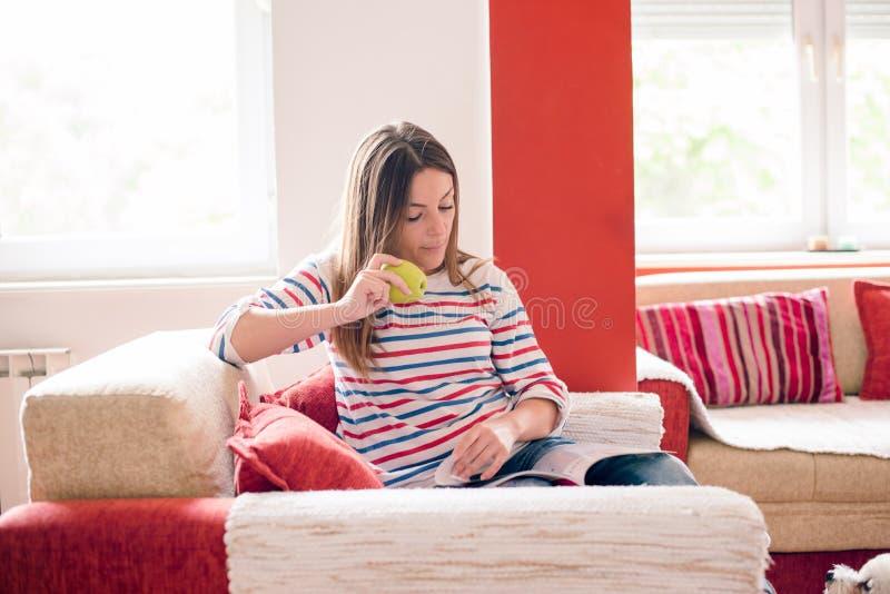 De jonge vrouw eet appel en leest tijdschrift stock afbeelding