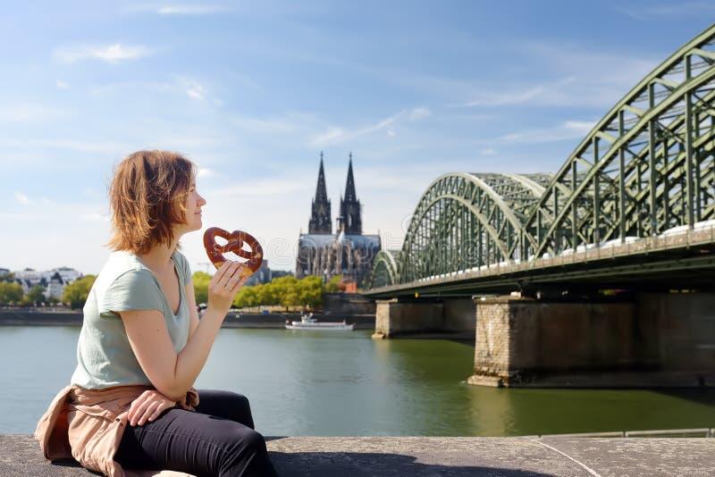 De jonge vrouw eet binnen traditionele pretzelzitting op dijk van Rijn op achtergrond van de Kathedraal van Keulen en Hohenzoller stock foto's