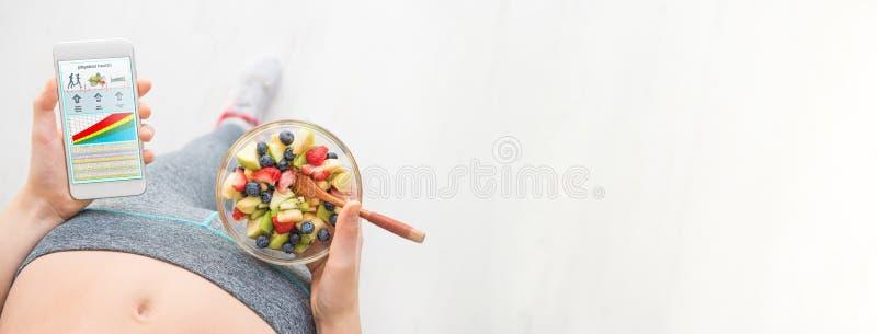 De jonge vrouw eet een fruitsalade en gebruikt een geschiktheid app op haar smartphone stock fotografie
