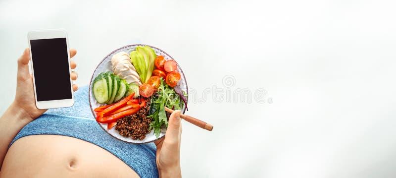 De jonge vrouw eet een gezond voedsel en gebruikt een geschiktheid app op haar smartphone na een training stock foto