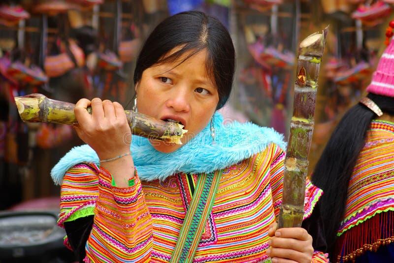De jonge vrouw eet een suikerriet royalty-vrije stock afbeeldingen