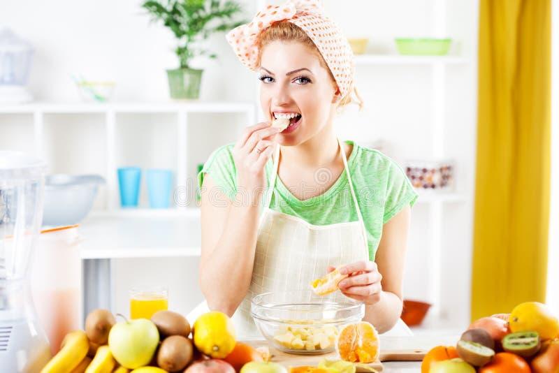 De jonge vrouw eet sinaasappelen royalty-vrije stock afbeeldingen