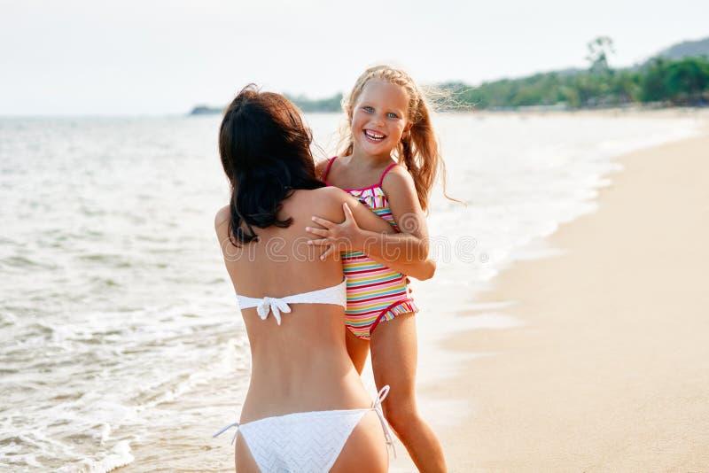 De jonge vrouw en haar vrij weinig dochter koesteren en glimlachen op het tropische strand royalty-vrije stock afbeelding