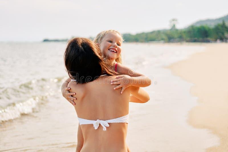 De jonge vrouw en haar vrij weinig dochter koesteren en glimlachen op het tropische strand stock afbeelding