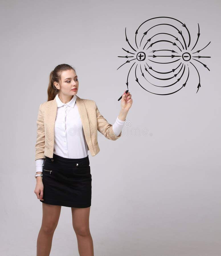 De jonge vrouw, fysicaleraar trekt een diagram van het elektrische veld stock foto