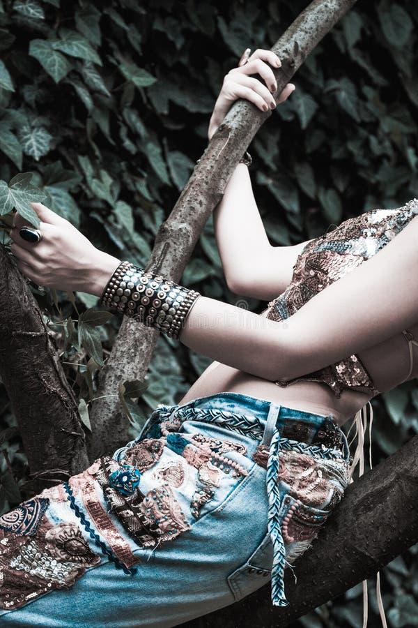 De jonge vrouw in geborduurde jeans en de glanzende hoogste close-up van de de zomermanier van de bohostijl zitten op boom royalty-vrije stock foto's