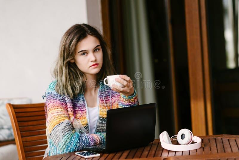 De jonge vrouw gebruikt een laptop computer op huisterras royalty-vrije stock foto's