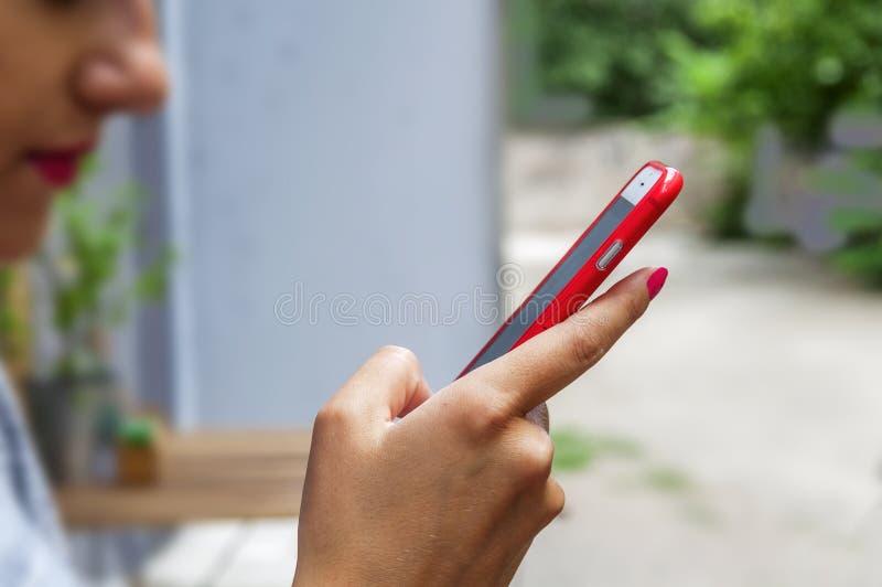 De in jonge vrouw gebruikt een slimme telefoon in het onduidelijke beeld van de koffiewinkel stock afbeeldingen