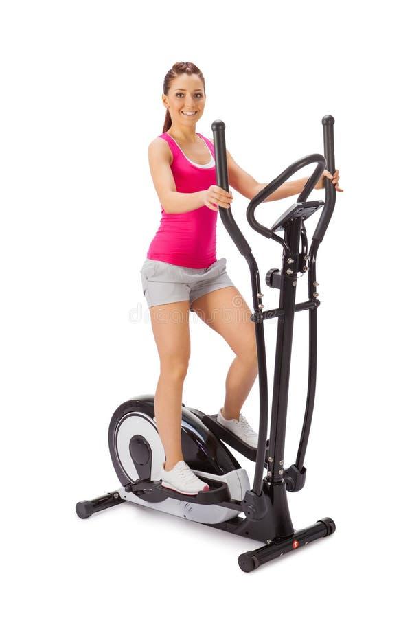 De jonge vrouw gebruikt elliptische dwarstrainer. stock foto's