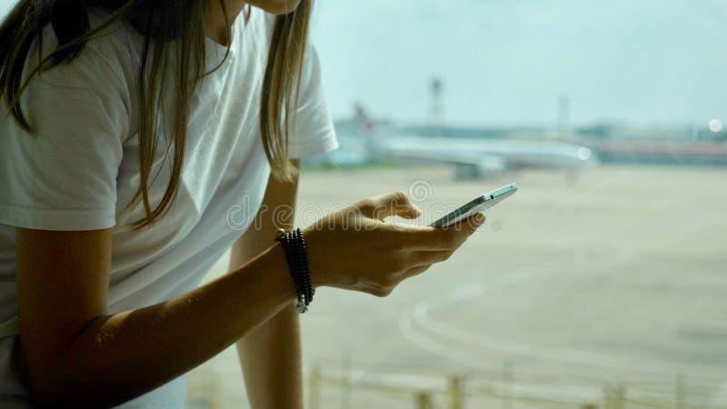 De jonge vrouw gebruikt slimme telefoon bij luchthaven met vliegtuig op de achtergrond royalty-vrije stock fotografie