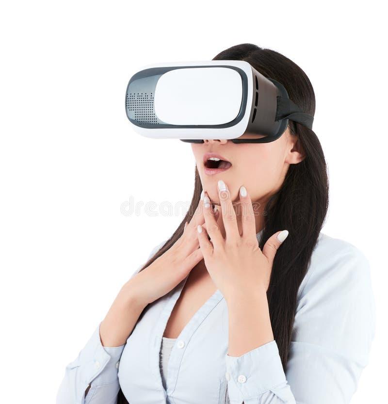 De jonge vrouw gebruikt VR-hoofdtelefoon op witte achtergrond stock fotografie