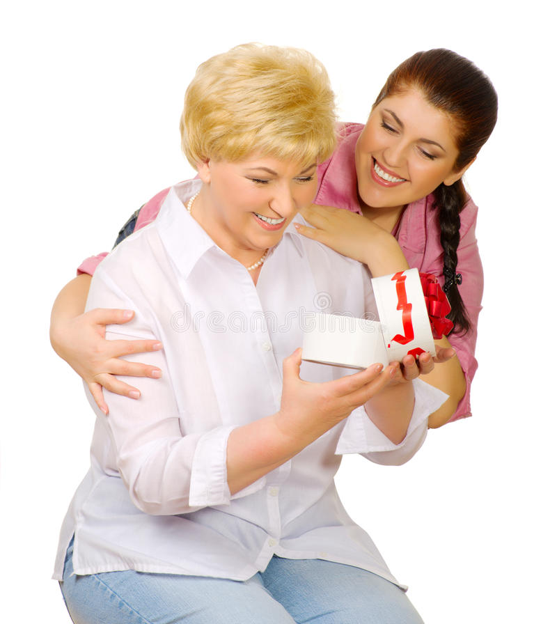 De jonge vrouw geeft gift aan haar moeder stock fotografie
