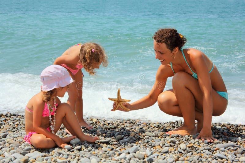 De jonge vrouw geeft zeester aan twee meisjes op strand stock afbeeldingen
