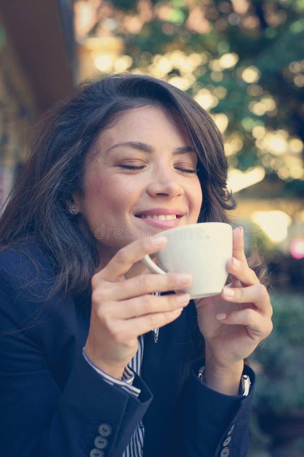 De jonge vrouw geniet van in koffie stock fotografie