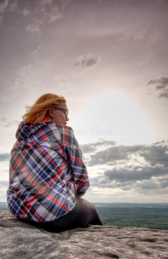 De jonge vrouw in gestreept jasje neemt een rust op rotsachtige top stock foto's