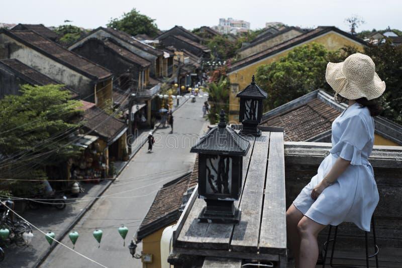 De jonge vrouw gezien de kant kijkt neer op een oude straat in Hoi An, Viet Nam royalty-vrije stock afbeeldingen