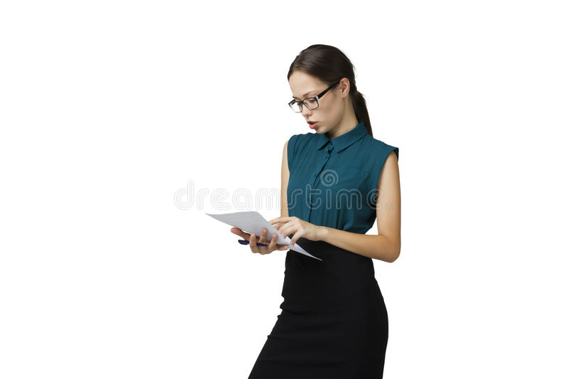 De jonge vrouw in glazen en een zwart pak leest het document op witte achtergrond stock afbeelding