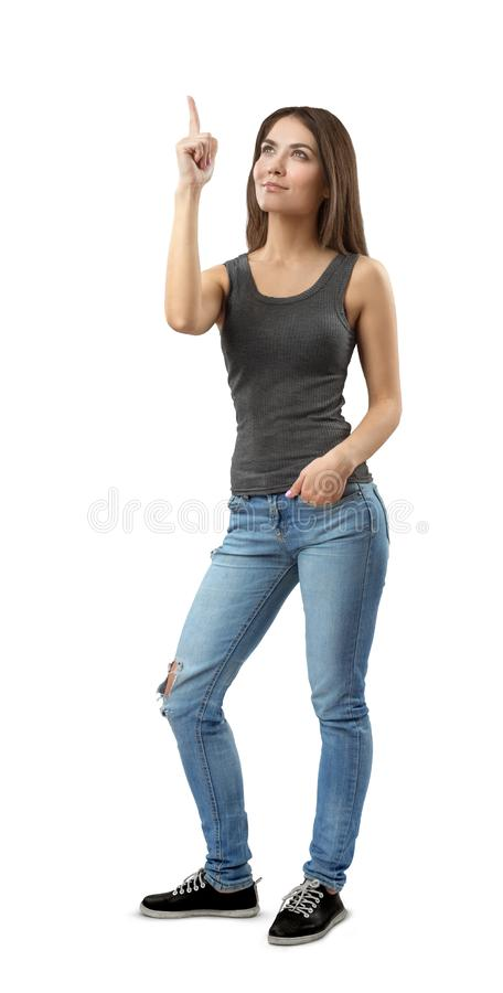 De jonge vrouw in grijze bovenkant en de jeans die zich in halve draai, één wijsvinger bevinden die, andere dienen zak in benadru royalty-vrije stock afbeelding