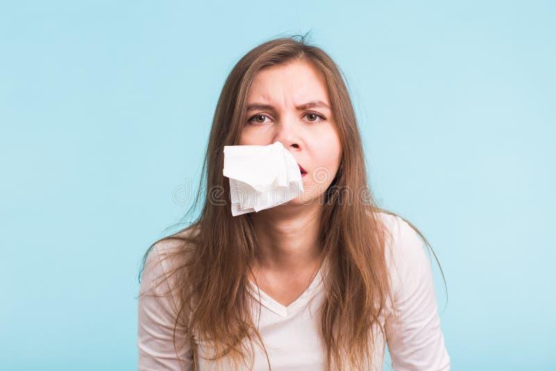 De jonge vrouw heeft een lopende neus op blauwe achtergrond stock fotografie
