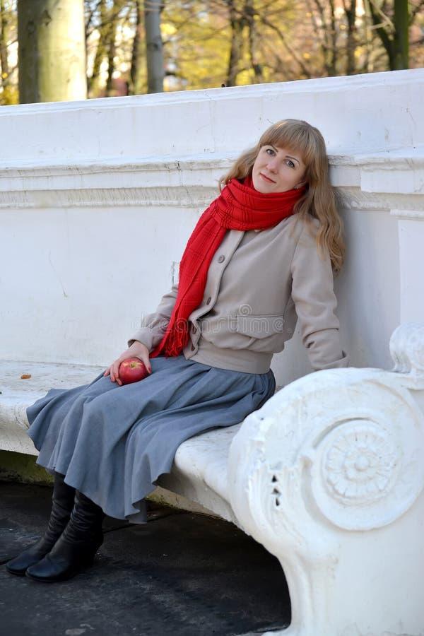 De jonge vrouw heeft een rust op een bank in het de herfstpark royalty-vrije stock afbeeldingen