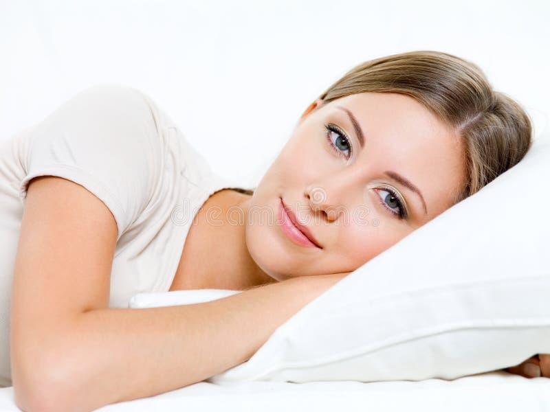 De jonge vrouw heeft een rust op het bed stock afbeelding