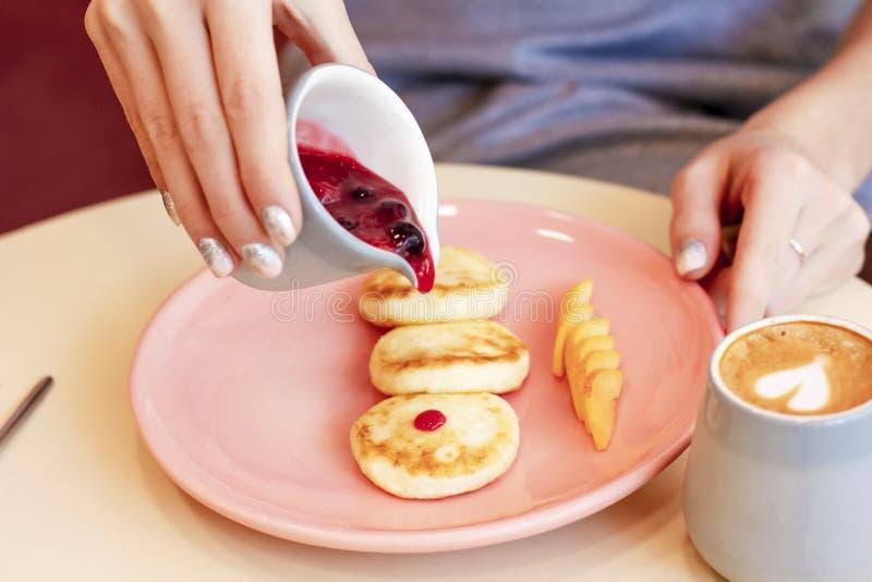 De jonge vrouw heeft Ontbijt in koffiekaastaarten met bessenjam stock foto