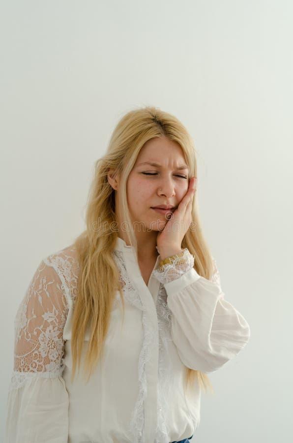 De jonge vrouw heeft tandpijn stock foto