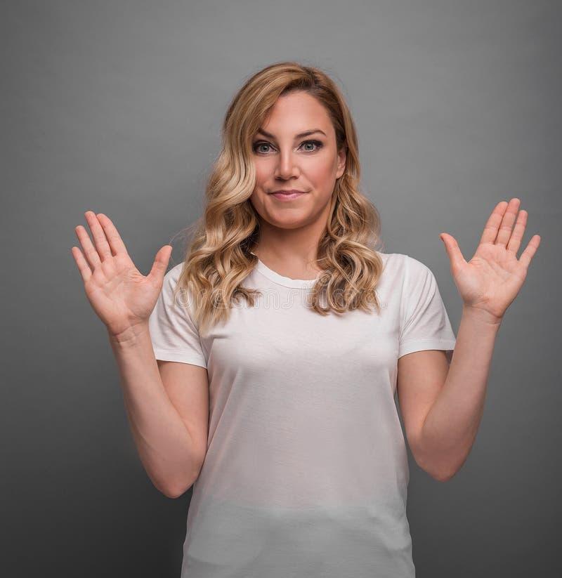 De jonge vrouw heft haar handen op die verrassing of ontkenning tonen royalty-vrije stock fotografie