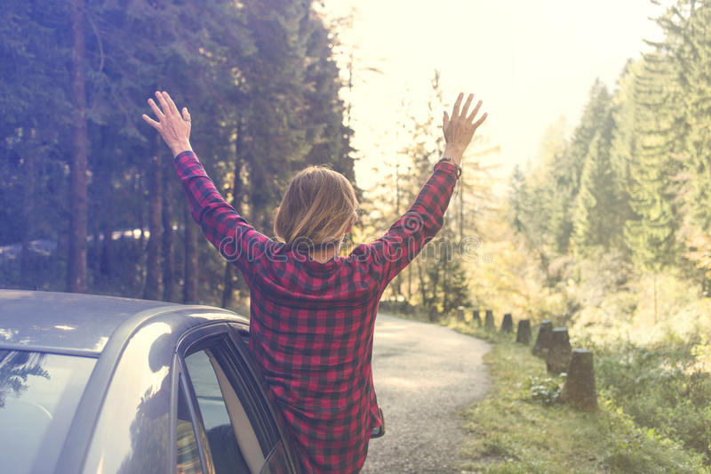 De jonge vrouw heft haar wapens aan de hemel op die uit het autoraam leunen stock afbeeldingen