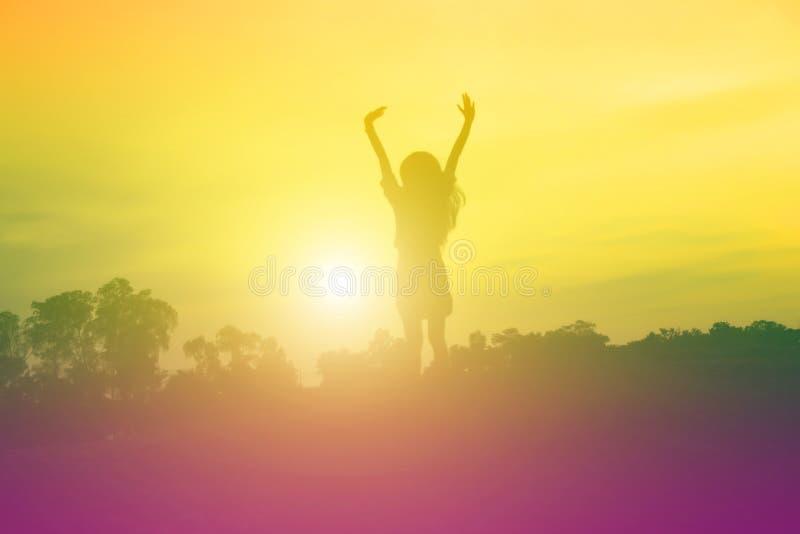 De jonge vrouw heft omhoog handen voor haar succes, Concept op Succes in het leven stock fotografie